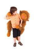 Weinig jongen omhelst een teddybeer Stock Foto's