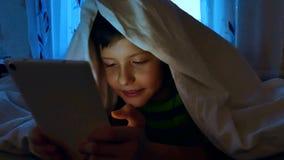 Weinig jongen onder de dekking bij nacht met een digitale tablet die online spelen spelen 7 van de oude kindjaar jongen die smart stock footage