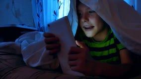 Weinig jongen onder de dekking bij nacht met een digitale tablet die online spelen spelen 7 van de oude kindjaar jongen die smart stock videobeelden