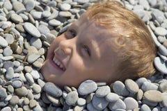 Weinig jongen onder ondiepe steen Royalty-vrije Stock Foto's