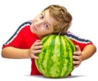 Weinig jongen onderzoekt de rijpheid van watermeloen Royalty-vrije Stock Foto