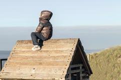 Weinig jongen op dak van houten plattelandshuisje stock afbeelding