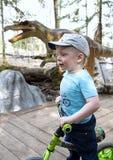 Weinig jongen op de achtergrond van de tekens met de beschrijving van een dinosaurus in het park van dinosaurussen royalty-vrije stock foto's