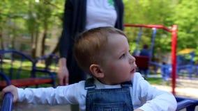 Weinig jongen op de carrousel op de speelplaats stock footage