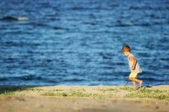 Weinig jongen op de heuvel met overzees op achtergrond stock foto
