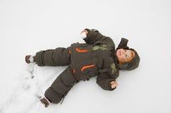 Weinig jongen is op de sneeuw Stock Afbeeldingen