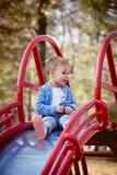 Weinig jongen op dia in park Stock Afbeelding