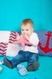Weinig jongen op een achtergrond van overzees decor met een stuk speelgoed Royalty-vrije Stock Foto's