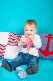 Weinig jongen op een achtergrond van overzees decor met een stuk speelgoed Stock Foto