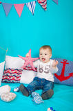 Weinig jongen op een achtergrond van overzees decor met een stuk speelgoed Royalty-vrije Stock Foto
