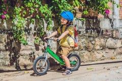 Weinig jongen op een fiets Gevangen in motie, op een vage oprijlaanmotie Peuterkind` s eerste dag op de fiets E stock foto