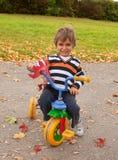 Weinig jongen op een fiets van kinderen Stock Afbeeldingen