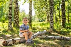 Weinig jongen op een gang in het hout Stock Fotografie