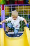Weinig jongen op een glijbaan in het park op een gang stock afbeelding