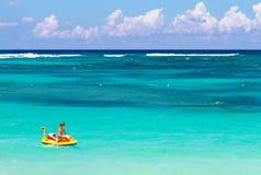 Weinig jongen op een opblaasbare boot op tropisch strand stock foto's