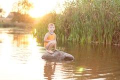 Weinig jongen op een rots in het meer bij zonsopgang royalty-vrije stock afbeeldingen