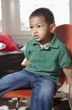 Weinig jongen op een stoel Stock Afbeelding