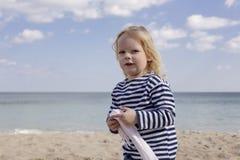 Weinig jongen op het strand in jeans en een vest gestreepte sweaters royalty-vrije stock fotografie