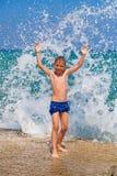 Weinig jongen op het strand met grote plonsen Royalty-vrije Stock Afbeeldingen