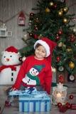 Weinig jongen op Kerstmis, het openen stelt voor Royalty-vrije Stock Afbeeldingen