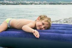 Weinig jongen op opblaasbare matras dichtbij overzees Stock Foto