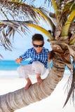 Weinig jongen op palm Stock Foto