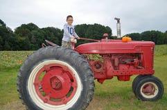 Weinig jongen op rode tractor Stock Afbeelding