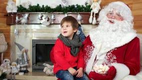 Weinig jongen op santa` s overlapping, kind die heilige vertellen Nicolas zijn Kerstmis, vakantieatmosfeer dit wenst stock video