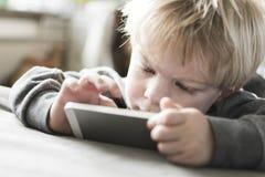 Weinig jongen op smartphone stock foto's