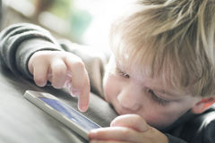 Weinig jongen op smartphone Stock Foto
