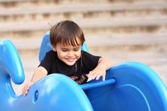 Weinig jongen op speelplaatsapparatuur Stock Fotografie