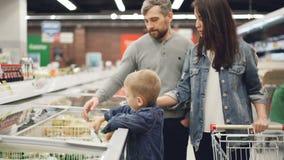 Weinig jongen opent diepvriezer en neemt pak bevroren groenten die dan het geven aan zijn papa terwijl binnen het winkelen stock videobeelden