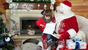 Weinig jongen opent zijn Kerstmisbrief, kindzitting op santasoverlapping, de woonplaats van heilige Nicolas van het jong geitjebe stock video