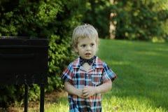 Weinig jongen in overhemd en vlinderdas in het park Stock Afbeelding
