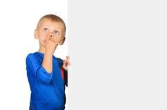 Weinig jongen plukt zijn neus met lege raad stock foto