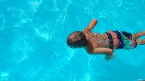 Weinig jongen in pool zwemmen en duikvluchten die onderwater stock video