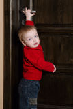 Weinig jongen probeert om deur te openen Stock Afbeeldingen
