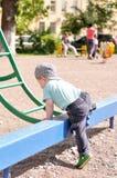 Weinig jongen probeert om op een ladder van kinderen te krijgen Stock Foto's