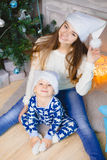 Weinig jongen in pyjama's en hoed van de Kerstman zitten glimlach met zijn zuster dichtbij Kerstmisboom Royalty-vrije Stock Foto's