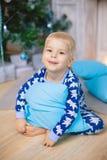 Weinig jongen in pyjama's met berenglimlach, zit en koestert blauw hoofdkussen Stock Afbeelding