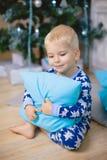 Weinig jongen in pyjama's met berenglimlach, zit en koestert blauw hoofdkussen Stock Fotografie