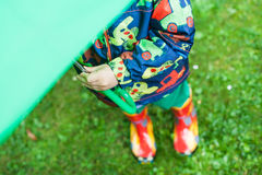 Weinig jongen in regenkleren en laarzen die onder groene paraplu verbergen Royalty-vrije Stock Fotografie