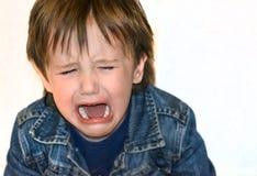 Weinig jongen schreeuwt op een witte achtergrond Woedeaanvalkind stock foto
