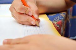 Weinig jongen schrijft vol overgave met een potlood in zijn notitieboekje Stock Fotografie
