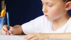 Weinig jongen schrijft vol overgave zijn thuiswerk stock video