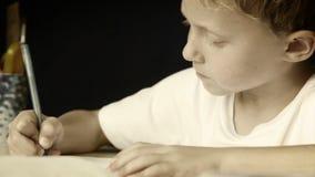 Weinig jongen schrijft vol overgave zijn thuiswerk: zwart-witte stijl stock footage