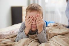 Weinig jongen sluit zijn ogen met zijn handen liggend op het bed met beige deken in de slaapkamer stock fotografie