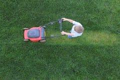 Weinig jongen snijdt een gras gebruikend grasmaaier Royalty-vrije Stock Afbeelding
