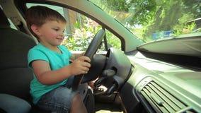 Weinig jongen speelt achter het wiel van een grote auto stock video