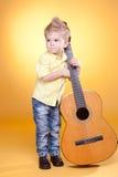 Weinig jongen speelt de gitaar Stock Foto